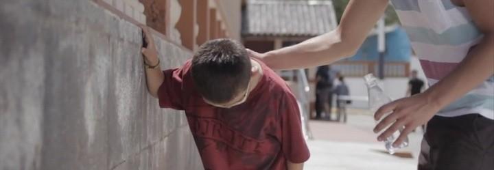 Cuando otro niño toma un descanso porque tiene sed, un hombre le da de beber