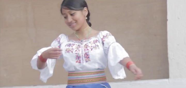 Blusa blanca con bordados multicolores, faldas (la exterior de color azul y la interior de color crema), faja de varios colores, alpargatas con capelladas negras, gualcas (collares), manillas (pulseras) de color rojo, aretes