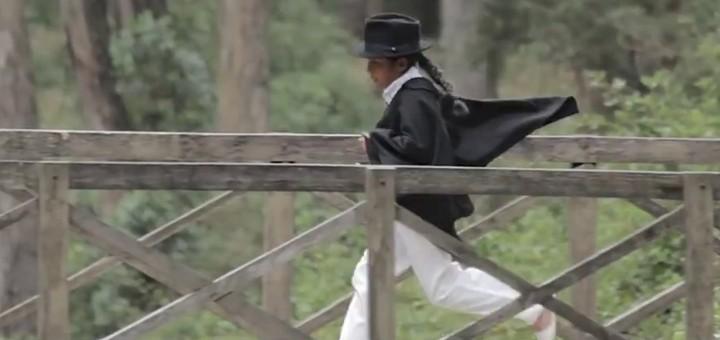 Sombrero de paño negro, trenza larga, camisa y pantalón de color blanco, poncho