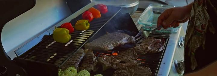 Preparan carne, chiles y elotes asados.